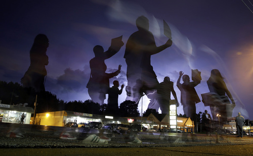 In this photo taken with a long exposure, protesters march in the street as lightning flashes in the distance in Ferguson, Mo., on Wednesday, Aug. 20, 2014. On Aug. 9, a white police officer fatally shot unarmed Michael Brown, a black 18-year-old, in the St. Louis suburb. (AP Photo/Jeff Roberson)