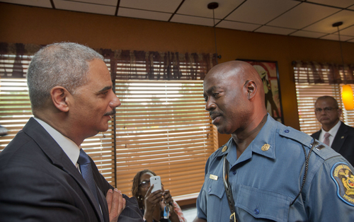 Attorney General Eric Holder speaks with Capt. Ron Johnson of the Missouri State Highway Patrol at Drake's Place Restaurant, Wednesday, Aug. 20, 2014, in Ferguson, Mo. Holder arrived in Missouri on Wednesday, a small group of protesters gathered outside the building where a grand jury could begin hearing evidence to determine whether a Ferguson police officer who shot 18-year-old Michael Brown should be charged in his death.   (AP Photo/Pablo Martinez Monsivais, Pool)