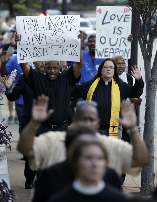 Protesters march to the Buzz Westfall Justice Center Wednesday, Aug. 20, 2014, in Clayton, Mo. A grand jury has begun hearing evidence as it weighs possible charges against the Ferguson police officer who fatally shot 18-year-old Michael Brown. (AP Photo/Jeff Roberson)