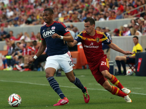 New England Revolution defender Darrius Barnes (25) dribbles the ball as Real Salt Lake midfielder Luis Gil (21) puts pressure on in the first half of an MLS soccer match on Friday, July 4, 2014, in Sandy, Utah. (AP Photo/Kim Raff)