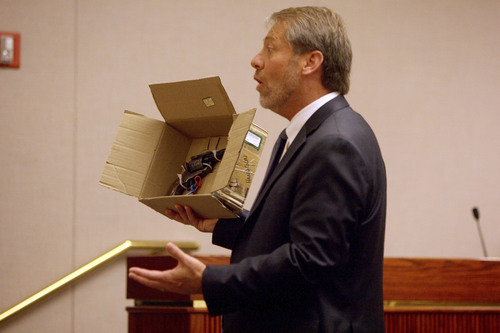 Uintah County Attorney G. Mark Thomas addresses the jury during closing arguments Friday, Aug. 22, 2014, in the murder trial for Jesse Anthony Saenz while holding the gun that investigators believe Saenz used to kill 22-year-old Elvis Zachary Olsen on April 21, 2013.