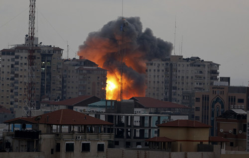A ball of fire rises from an explosion on al-Zafer apartment tower following an Israeli air strike in Gaza City, in the northern Gaza Strip, Saturday, Aug. 23, 2014. Israeli aircraft fired two missiles at a 12-story apartment tower in downtown Gaza City on Saturday, collapsing the building, sending a huge fireball into the sky and wounding at least 22 people, including 11 children, witnesses and Palestinian officials said. (AP Photo/Adel Hana)