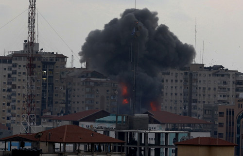 A ball of fire and smoke rise from an explosion on al-Zafer apartment tower following an Israeli air strike in Gaza City, in the northern Gaza Strip, Saturday, Aug. 23, 2014. Israeli aircraft fired two missiles at a 12-story apartment tower in downtown Gaza City on Saturday, collapsing the building, sending a huge fireball into the sky and wounding at least 22 people, including 11 children, witnesses and Palestinian officials said. (AP Photo/Adel Hana)