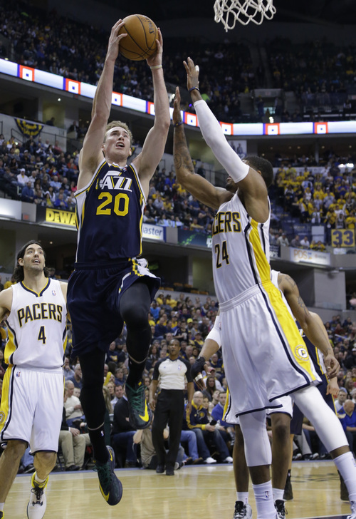Utah Jazz guard Gordon Hayward, left, shoots over Indiana Pacers forward Paul George during the second half of an NBA basketball game in Indianapolis, Sunday, March 2, 2014. The Pacers defeated the Jazz 94-91.  (AP Photo/Michael Conroy)