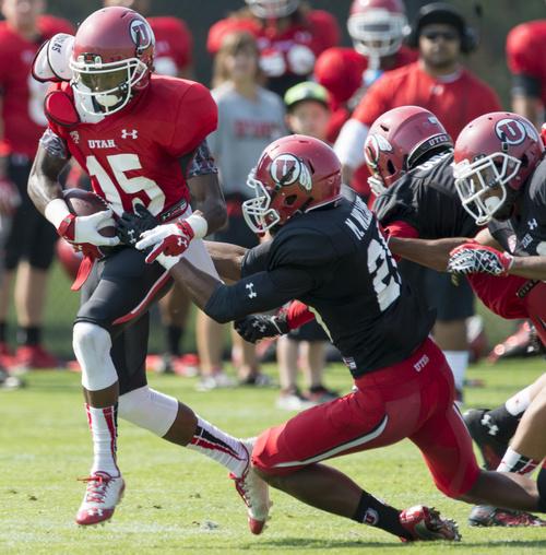 Rick Egan  |  The Salt Lake Tribune  Marcus Williams (20) tries to bring down, Dominique Hatfield (15) during the University of Utah football practice, Saturday, August 9, 2014