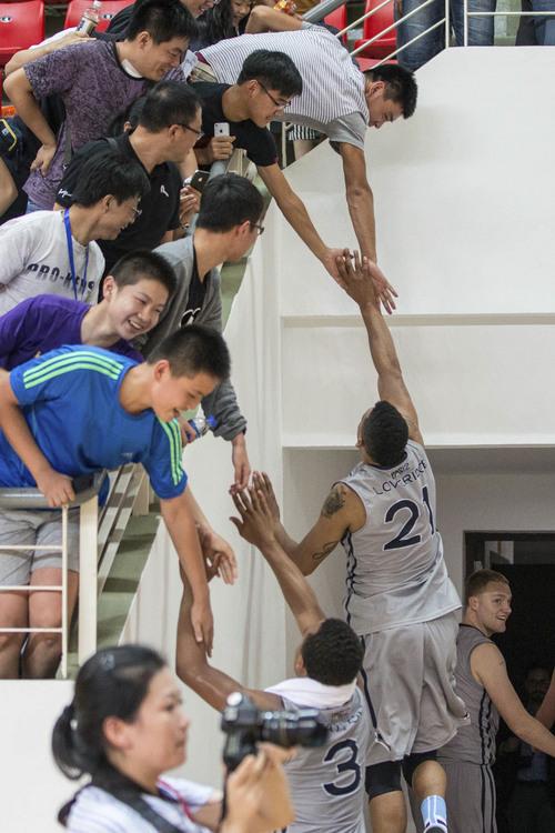 Kory Mortensen  |  Utah Athletics  Utah small forward Jordan Loveridge gives five to basketball fans in Shanghai.