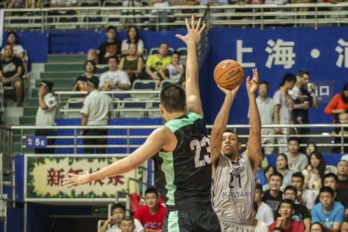 Kory Mortensen  |  Utah Athletics  Utah small forward Jordan Loveridge shoots over a defender in Shanghai.