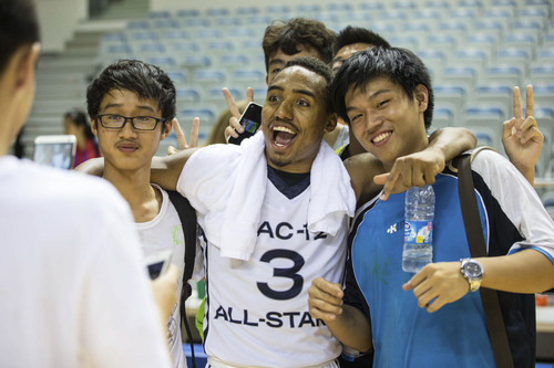 Kory Mortensen  |  Utah Athletics  Utah point guard Brandon Taylor poses for a photo with fans in Shanghai.