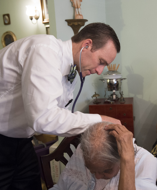 Dr. Eric De Jonge of Washington Hospital Center conducts a Medicare examines patient Beatrice Adams during a house call at her home in Washington, Thursday, Aug. 7, 2014. (AP Photo/Molly Riley)