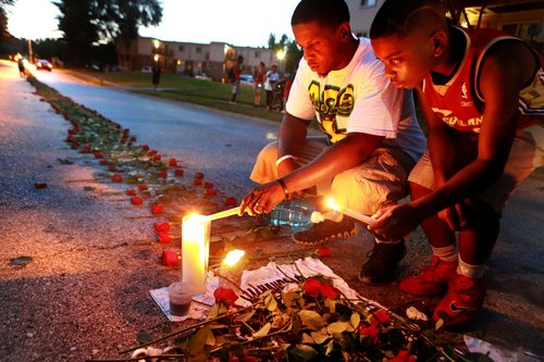 In this photo taken on Thursday, Aug. 21, 2014, Theo Murphy, left, of Florissant, Mo., and his brother Jordan Marshall, 11, light candles at a memorial on Canfield Drive in Ferguson, Mo., where where unarmed Michael Brown was fatally shot by Ferguson Police Officer Darren Wilson. A small group of people, who preferred to remain anonymous,laid roses along the middle of the road that stretched about 60 yards. (AP Photo/St. Louis Post-Dispatch, Christian Gooden)  EDWARDSVILLE INTELLIGENCER OUT; THE ALTON TELEGRAPH OUT