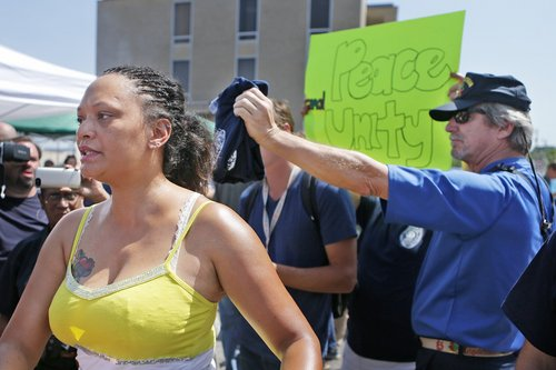 """Sondra Fifer, of St. Louis, voices her disagreement with the rally for Ferguson police Officer Darren Wilson on Saturday, Aug. 23, 2014, at Barney's Sports Pub in St. Louis. """"I'm not against officers, I'm against police brutality,"""" Fifer said. Ferguson's streets remained peaceful as tensions between police and protesters continued to subside after nights of violence and unrest that erupted when Wilson, a white police officer, fatally shot Michael Brown, an unarmed black 18-year-old. (AP Photo/St. Louis Post-Dispatch, Huy Mach)  EDWARDSVILLE INTELLIGENCER OUT; THE ALTON TELEGRAPH OUT"""