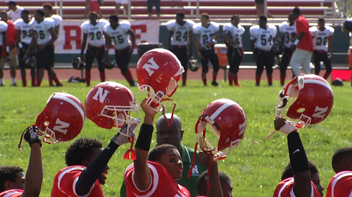 In this image taken from video on Saturday, Aug. 23, 2014, Normandy High School football players, students and parents observe a moment of silence for Michael Brown before the start of the first game of the school year, in Ferguson, Mo. Brown, 18, was killed by a Ferguson police officer on Aug. 9, eight days after he graduated from the high school. (AP Photo/Alex Sanz)