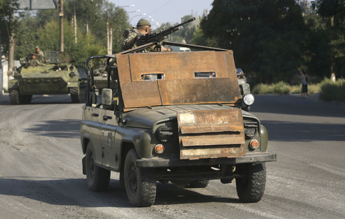 FILE - This is a Sunday, Aug. 17, 2014  file photo of Pro-Russian rebels as they ride on an armored jeep in the town of Krasnodon, eastern Ukraine.  A column of several dozen heavy vehicles, including tanks and at least one rocket launcher, rolling through rebel-held territory on Aug. 17. AP reporters say convoys of military weaponry and supplies have been coming from the direction of Russia into rebel-held Ukraine. Rebel fighters also described how Russian border guards did nothing to stop them. Associated Press reporters in the eastern Ukrainian town of Krasnodon observed three such convoys last week. (AP Photo/Sergei Grits, File)