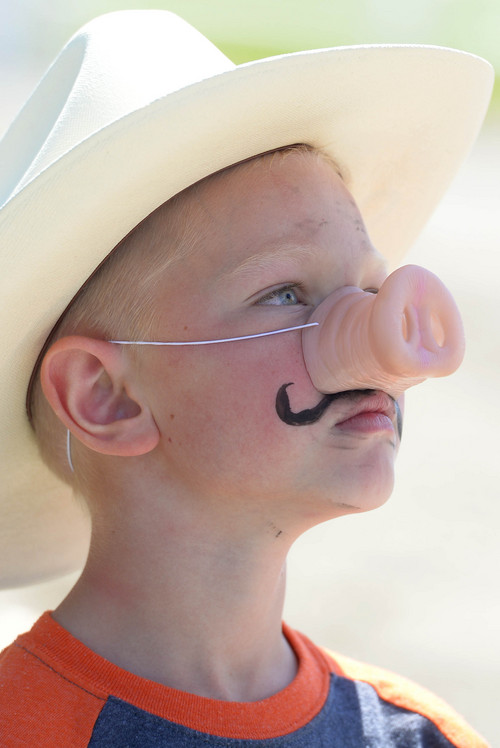 Leah Hogsten  |  The Salt Lake Tribune Talen Mortensen, 6, of Eagle Mountain sports a mustache with his snout. Thanksgiving Point celebrated all things pig, especially bacon, with its Bacon Bash, Saturday, August 23, 2014. The event included games and pony and wagon rides.