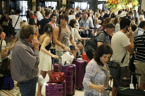 In this Sunday, Aug. 17, 2014 photo, people wait in line to check into the Bellagio, in Las Vegas. This year, hotels will take in a record $2.25 billion in revenue from fees and surcharges, 6 percent more than in 2013 and nearly double that of a decade ago, according to a new study. Nearly half of the increase can be attributed to new surcharges and hotels increasing the amounts of existing fees. (AP Photo/John Locher)