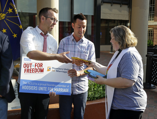 Rev. Melody Merida, of the Life Journey Church, hands out signed heart-shaped cards to Greg Hasty, left, and CJ Vallero following at a rally in Indianapolis, Monday, Aug. 25, 2014 for gay couples that are part of a court hearing on the challenge to Indiana's same-sex marriage ban. Nearly 100 supporters gathered at the City Market in downtown Indianapolis to see off some of the plaintiffs as they left to attend legal arguments before a federal appeals court on Tuesday.  (AP Photo/Michael Conroy)
