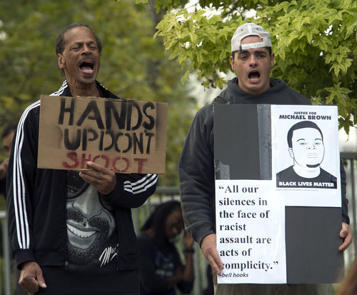 Rick Egan  |  The Salt Lake Tribune  Oscar Ross, and Damon Harris shout along with other protesters, in solidarity with Mike Brown, Dillon Taylor, Danielle Willard and others who they feel were killed unjustly by police. Monday, August 25, 2014.