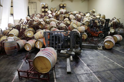 Some of the hundreds of earthquake damaged wine barrels cover and toppled a pair of forklifts at the Kieu Hoang Winery, Monday, Aug. 25, 2014, in Napa, Calif. A powerful earthquake that struck the heart of California's wine country caught many people sound asleep, sending dressers, mirrors and pictures crashing down around them and toppling wine bottles in vineyards around the region. The magnitude-6.0 quake struck at 3:20 a.m. PDT Sunday near the city of Napa. (AP Photo/Eric Risberg)