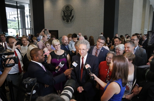 ACLU attorney Ken Faulk, center, talks to reporters surrounded by plaintiffs and supporters of gay marriage, after Faulk participated in a hearing before the 7th U.S. Circuit Court of Appeals on the challenges to Indiana and Wisconsin's gay marriage ban Tuesday, Aug. 26, 2014, in Chicago. (AP Photo/Charles Rex Arbogast)