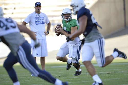 Chris Detrick  |  The Salt Lake Tribune Brigham Young Cougars quarterback Taysom Hill (4) looks to pass the ball as Brigham Young Cougars head coach Bronco Mendenhall looks on during a scrimmage at LaVell Edwards Stadium Friday August 15, 2014.