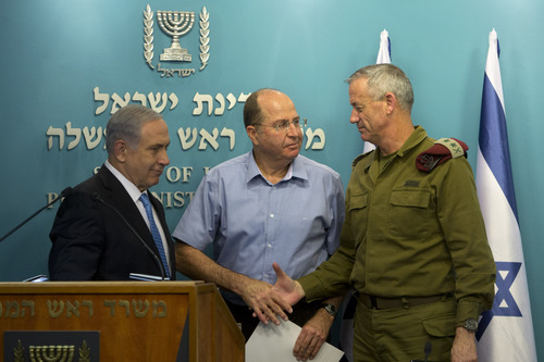 Israeli Prime Minister Benjamin Netanyahu, left, stands with Israel's Defense Minister Moshe Yaalon, center, and Israeli Chief of Staff Lt. Gen. Benny Gantz, during a press conference at the prime minister's office in Jerusalem, Wednesday, Aug. 27, 2014.  Israel's prime minister declared victory Wednesday in the recent war against Hamas in the Gaza Strip, saying the military campaign had dealt a heavy blow and a cease-fire deal gave no concessions to the Islamic militant group. (AP Photo/Sebastian Scheiner)