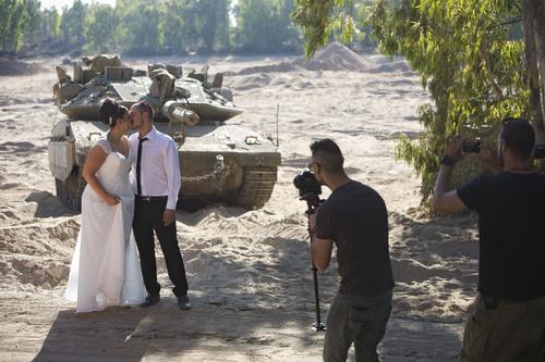 Israeli couple, Noga and Moshiko Siho, have their wedding photo taken in an army staging area on the Israeli Gaza border, near Kibbutz Yad Mordechai, Israel, Wednesday, Aug. 27, 2014. (AP Photo/Oded Balilty)