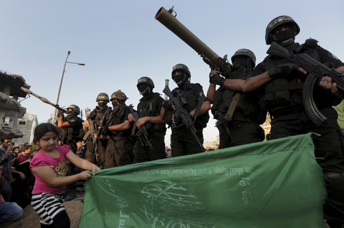 A Palestinian girl waves a green Islamic flag while walking in front of masked militants of Izzedine al-Qassam Brigades, military wing of Hamas, during a victory rally at the debris of destroyed houses in Shijaiyah, neighborhood of Gaza City, in the northern Gaza Strip, Wednesday, Aug. 27, 2014. An open-ended cease-fire between Israel and Palestinian militants in the Gaza Strip was holding Wednesday. (AP Photo/Adel Hana)