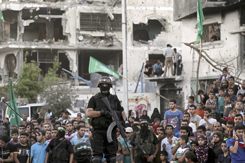 Palestinian masked militants of Izzedine al-Qassam Brigades, military wing of Hamas, and their supporters  celebrate during a victory rally at the debris of destroyed houses in Shijaiyah, neighborhood of Gaza City, in the northern Gaza Strip, Wednesday, Aug. 27, 2014. An open-ended cease-fire between Israel and Palestinian militants in the Gaza Strip was holding Wednesday. (AP Photo/Adel Hana)