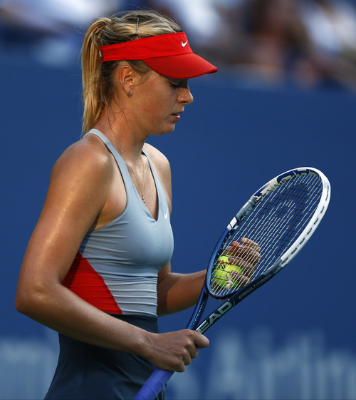Maria Sharapova, of Russia, adjusts the strings on her racket after a point against Alexandra Dulgheru, of Romania, during the second round of the 2014 U.S. Open tennis tournament, Wednesday, Aug. 27, 2014, in New York. (AP Photo/Matt Rourke)