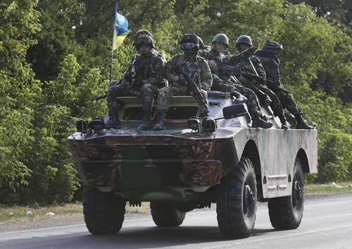 Ukrainian soldiers ride atop an APC near the village of Sakhanka, eastern Ukraine, Wednesday, Aug. 27, 2014. Separatist rebels shelled a town of Novoazovsk in southeastern Ukraine on Wednesday, raising fears they are launching a counter-offensive on government-held parts of the region, one day after the leaders of Ukraine and Russia met to discuss the escalating crisis. (AP Photo/Sergei Grits)