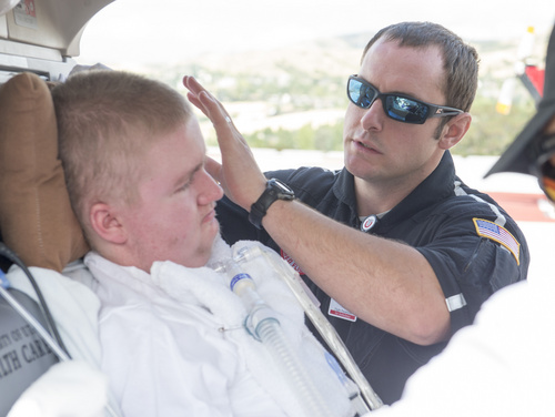 Rick Egan  |  The Salt Lake Tribune  Flight paramedic Jordan Fielding secures Sean Anderson in the helicopter for his flight back to Stansbury Park, at the University of Utah Medical Center, Wednesday, August 27, 2014.  Sean was born with muscular dystrophy and is autistic. He loves hospitals, ambulances and helicopters. AirMed granted Sean's wish to fly in a helicopter.