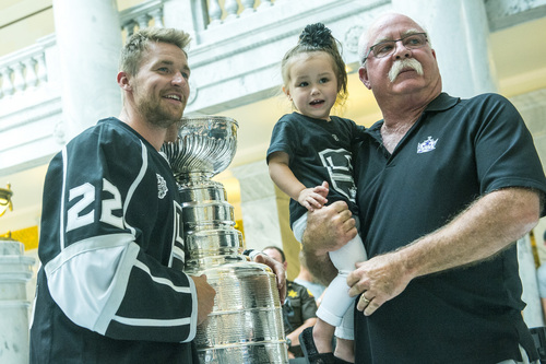 Chris Detrick  |  The Salt Lake Tribune Los Angeles Kings' Trevor Lewis poses for a picture with Brian Welty and his granddaughter Nevaeh Moore, 2, of Salt Lake City,  and the Stanley Cup at the Utah State Capitol Wednesday August 27, 2014. Lewis is a Salt Lake City native who played for Brighton's club team as a freshman in 2002. Hockey tradition dictates that each member of the winning team gets custody of the Cup for one day.