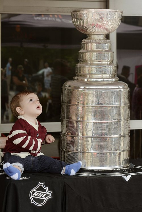 Charlie Owens, 8 months, has his photo taken with the Stanley Cup at Prospera Place in Kelowna, British Columbia, on Friday Aug. 22, 2014. Los Angeles Kings goalie coach Kim Dillabaugh--a former WHL Kelowna Rockets goalie--brought the cup to Kelowna. (AP Photo/The Canadian Press, Gary Nylander, Kelowna Daily Courier)