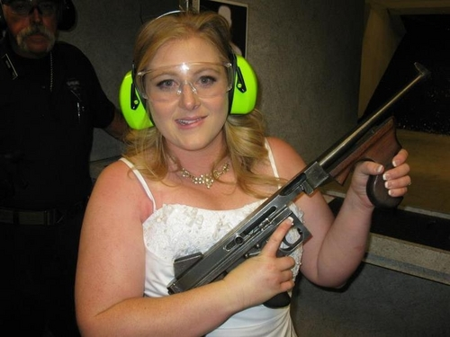 "FILE - This July 28, 2012 file photo provided by Bob MacDuff shows Lindsae MacDuff holding an automatic weapon at the Gun store in Las Vegas after her ""shotgun wedding."" Tourists from Japan flock to ranges in Waikiki, Hawaii, and the dozen or so that have cropped up in Las Vegas offer bullet-riddled bachelor parties and literal shotgun weddings, where newly married couples can fire submachine gun rounds and pose with Uzis and ammo belts. (AP Photo/Bob MacDuff, FILE)"