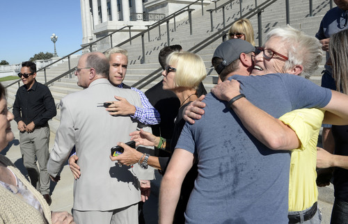 Al Hartmann  |  The Salt Lake Tribune LGBT protesters known as the ìCapitol 13î hug each other in support in front of the Utah Capitol building Thursday August 28, 2014. They were arrested at the Legislature in February and charged Wednesday with disturbing a meeting, a class B misdemeanor. They collectively announced their not guilty plea.
