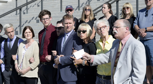 "Al Hartmann  |  The Salt Lake Tribune LGBT protesters known as the ""Capitol 13"" stand arm in arm in front of the Utah Capitol building with their lawyers Thursday August 28, 2014, to collectively announce their not guilty plea.  They were arrested at the Legislature in February for disturbing a meeting, a class B misdemeanor, but were just charged Wednesday.  Attorney Ron Yengich, right, holds a copy of the Utah Constitution and comments on the charges."