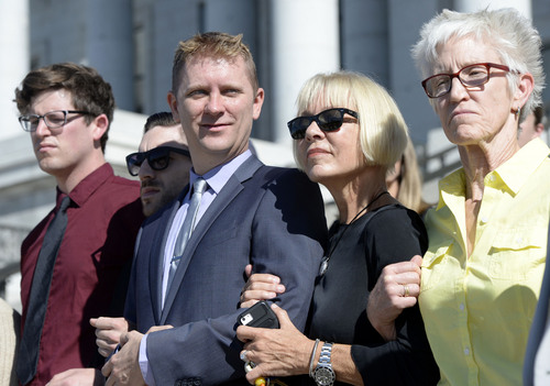 "Al Hartmann  |  The Salt Lake Tribune LGBT protesters known as the ""Capitol 13"" stand arm in arm in front of the Utah Capitol building with their lawyers Thursday August 28, 2014, to collectively announce their not guilty plea.  They were arrested at the Legislature in February for disturbing a meeting, a class B misdemeanor, but were just charged Wednesday."