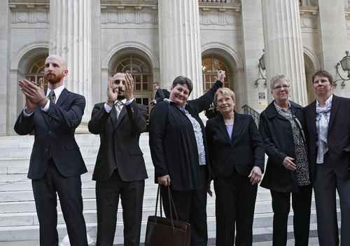 FILE - Plaintiffs challenging Utah's gay marriage ban, from left, Derek Kitchen, his partner Moudi Sbeity, Kate Call, her partner Karen Archer, Laurie Wood and her partner Kody Partridge stand together after leaving court following a hearing at the U.S. Circuit Court of Appeals in Denver, Thursday, April 10, 2014.  (AP Photo/Brennan Linsley)