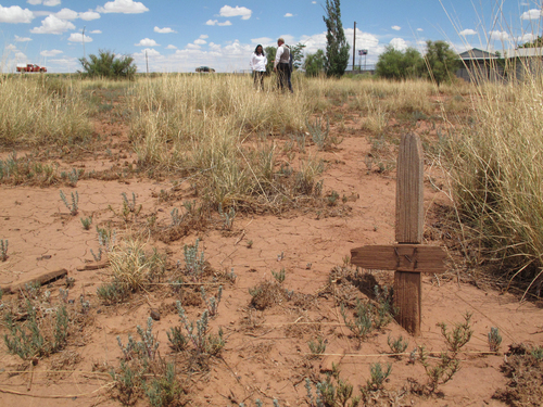 This July 9, 2014 photos shows part of a wooden cross sticking out of the ground at a cemetery in Winslow, Arizona. Local historic preservation Commissioner Gail Sadler has made it her mission to unearth the identities of roughly 600 people buried there and help their descendants reconnect with a lost part of their history. (AP Photo/Felicia Fonseca)