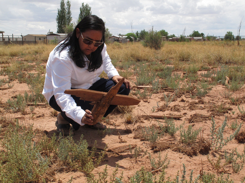 This July 9, 2014 photo shows Navajo archaeologist Kim Mangum picking up a wooden cross at a cemetery in Winslow, Arizona. Local historic preservation Commissioner Gail Sadler has made it her mission to unearth the identities of roughly 600 people buried there and help their descendants reconnect with a lost part of their history. (AP Photo/Felicia Fonseca)