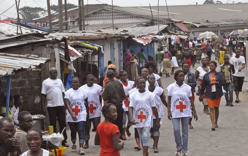 Abbas Dulleh  |  The Associated Press Red Cross workers on Wednesday walk through a section of West Point, an area that has been hit hard by the Ebola virus, with residents not allowed to leave as government forces clamp down on movement to prevent the spread of Ebola, in  Monrovia, Liberia. The Ebola outbreak in West Africa eventually could exceed 20,000 cases, more than six times as many as are now known, the World Health Organization said Thursday. A new plan released by the U.N. health agency to stop Ebola also assumes that the actual number of cases in many hard-hit areas may be two to four times higher than currently reported.