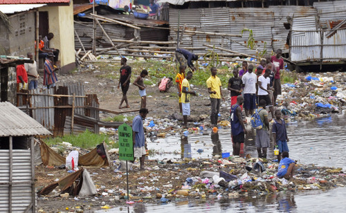 People stand on the shoreline near a sign reading 'NO DUMPING', amongst rubbish at West Point, a area heavily effected by the  Ebola virus, with residence not being  allowed to leave West Point,  as government forces clamp down on movement to prevent the spread of Ebola, in  Monrovia, Liberia, Wednesday, Aug. 27, 2014. Health officials in Liberia said the other two recipients of ZMapp in Liberia — a Congolese doctor and a Liberian physician's assistant, have recovered. Both are expected to be discharged from an Ebola treatment center on Friday, said Dr. Moses Massaquoi, a Liberian doctor with the treatment team. (AP Photo/Abbas Dulleh)