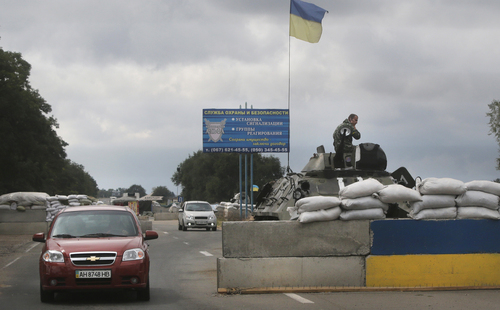 """Ukrainian forces guard  a checkpoint in the town of Mariupol, eastern Ukraine, Thursday, Aug. 28, 2014. Ukraine's president Petro Poroshenko called an emergency meeting of the nation's security council and canceled a foreign trip Thursday, declaring that """"Russian forces have entered Ukraine,"""" as concerns grew about the opening of a new front in the conflict. (AP Photo/Sergei Grits)"""