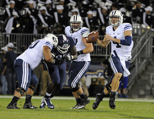 BYU quarterback Taysom Hill (4) looks to pass during the first half of an NCAA college football game against Connecticut in East Hartford, Conn., Friday, Aug. 29, 2014. (AP Photo/Fred Beckham)