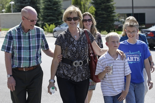 Jan Harding, center, walks with members of her family after a news conference in Salt Lake City on Friday, Aug. 29, 2014. Jan Harding, the Utah woman who nearly died after unknowingly drinking iced tea mixed with chemicals spoke publicly for the first time Friday, saying she hopes the incident is a wake-up call for restaurants. She spent almost two weeks in a Salt Lake City hospital after drinking a single sip of iced tea at Dickey's Barbecue in South Jordan, a Salt Lake City suburb. (AP Photo/Rick Bowmer)