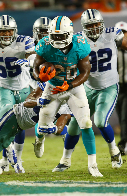 Miami Dolphins running back Knowshon Moreno (28)  breaks up a a tackle by Dallas Cowboys defensive back Johnny Thomas (47) during the first half of an NFL preseason football game Saturday, Aug. 23, 2014, in Miami Gardens, Fla. (AP Photo/J Pat Carter)