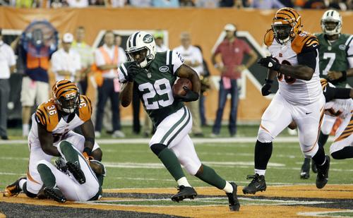 New York Jets running back Bilal Powell (29) runs away from Cincinnati Bengals defensive tackle Brandon Thompson (98) in the first half of an NFL preseason football game, Saturday, Aug. 16, 2014, in Cincinnati. (AP Photo/Tom Uhlman)