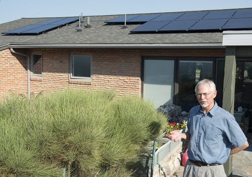 Rick Egan  |  The Salt Lake Tribune | File photo Stan Holmes talks in July about the solar panels he installed on his Salt Lake City home. The Utah Public  Service Commission has rejected a proposal from Rocky Mountain Power to require solar customers like Holmes to pay an additional monthly fee.
