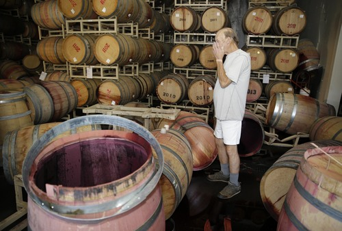 File - This Aug. 24, 2014 file photo shows winemaker Tom Montgomery standing in wine as he reacts to seeing damage following an earthquake at the B.R. Cohn Winery barrel storage facility in Napa, Calif. Napa Valley's seismically reinforced winery buildings generally held up to the largest earthquake to hit Northern California in a quarter-century, but the precious wine piled inside often did not. (AP Photo/Eric Risberg, file)
