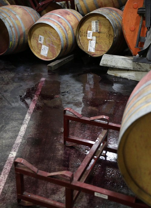 File - This Aug. 25, 2014 file photo shows wine leaking from some of the hundreds of earthquake damaged wine barrels at the Kieu Hoang Winery in Napa, Calif. Napa Valley's seismically reinforced winery buildings generally held up to the largest earthquake to hit Northern California in a quarter-century, but the precious wine piled inside often did not. (AP Photo/Eric Risberg, file)